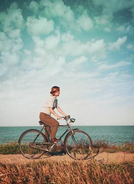Mark Owen BLONDE GIRL RIDING BICYCLE BY OCEAN Women