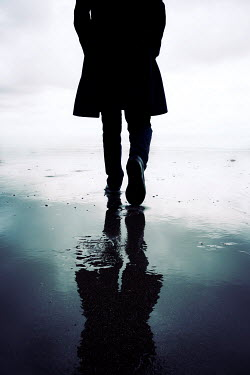 Tim Robinson SILHOUETTED MAN IN COAT WALKING ON BEACH Men