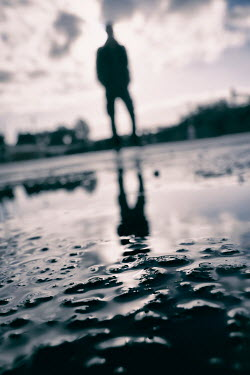 Tim Robinson SILHOUETTED MAN STANDING BY PUDDLE Men