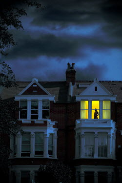 Miguel Sobreira SILHOUETTED WOMAN AT WINDOW OF HOUSE AT NIGHT Women