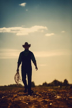 Magdalena Russocka cowboy with lasso walking in field