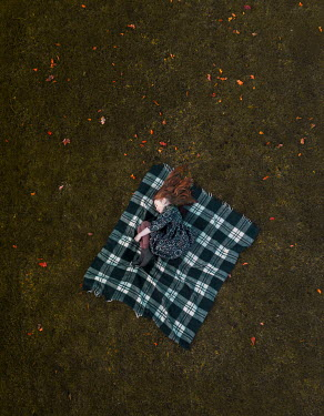 Mary Wethey GILR LYING ON BLANKET OUTSIDE IN AUTUMN Children