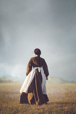 Joanna Czogala HISTORICAL WOMAN IN APRON WALKING IN COUNTRYSIDE Women
