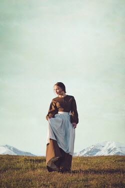 Joanna Czogala HISTORICAL WOMAN IN COUNTRYSIDE WITH SNOWY MOUNTAINS Women