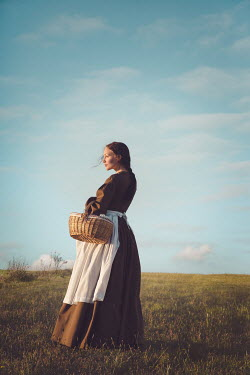 Joanna Czogala WOMAN STANDING IN COUNTRYSIDE WITH BASKET Women
