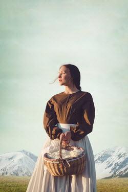 Joanna Czogala WOMAN BY SNOWY MOUNTAINS CARRYING BASKET Women
