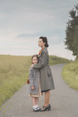 Joanna Czogala RETRO MOTHER HUGGING DAUGHTER ON COUNTRY LANE Children