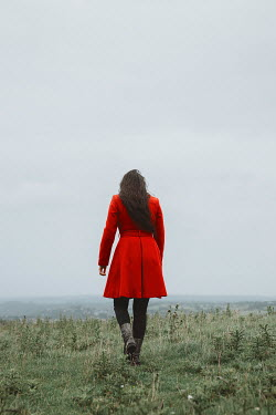 Shelley Richmond BRUNETTE WOMAN WITH RED COAT WALKING IN COUNTRYSIDE Women