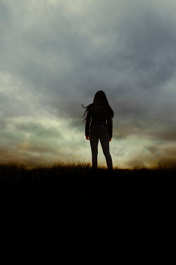 Shelley Richmond SILHOUETTED GIRL STANDING IN COUNTRYSIDE AT DUSK Women