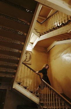 Daniil Kontorovich WOMAN DESCENDING STAIRCASE IN OLD BUILDING Women
