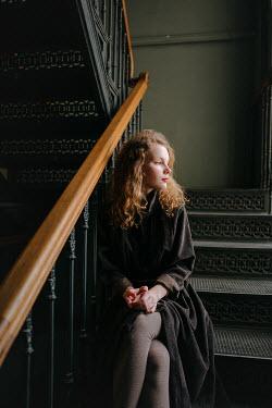 Daniil Kontorovich SERIOUS GIRL SITTING ON WROUGHT IRON STAIRCASE Women
