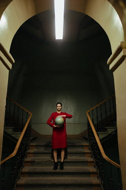 Daniil Kontorovich WOMAN STANDING ON STAIRCASE HOLDING GLOBE Women