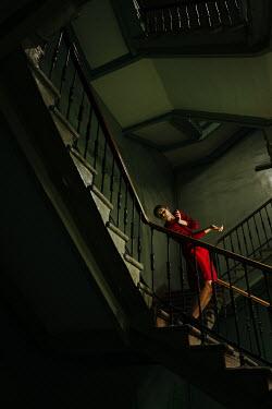 Daniil Kontorovich WOMAN IN RED DRESS POSING ON STAIRCASE Women