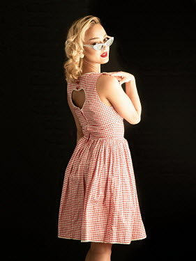 Elisabeth Ansley Young woman in 1950s dress and sunglasses on black background