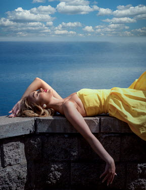 Elisabeth Ansley Young woman in yellow dress lying on stone wall