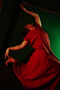 Daniil Kontorovich Young woman in red dress dancing in shadow