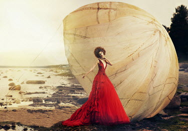Kirill Sakryukin Young woman in red dress with parachute on beach