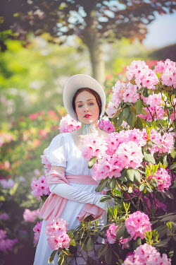 Joanna Czogala Young woman with Victorian bonnet and dress by bush with pink flowers