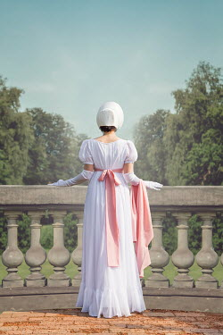 Joanna Czogala Young woman in Victorian bonnet and dress by stone banister
