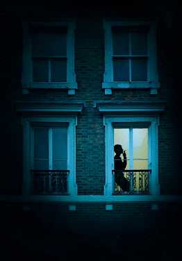 Lyn Randle Silhouette of man smoking in window of apartment