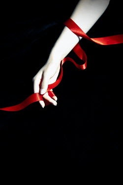 Miguel Sobreira Woman's arm wrapped in red ribbon