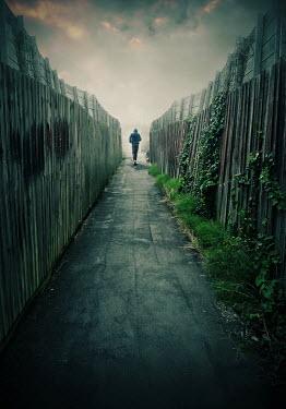 Lyn Randle Young man in hoodie walking in alley