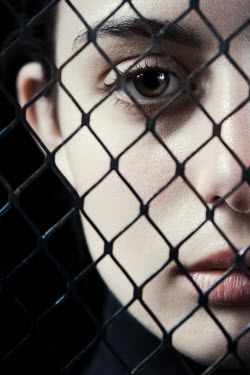 Magdalena Russocka young woman in black behind mesh fence