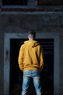 Paolo Martinez Young man in yellow hoodie at doorway to abandoned house