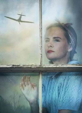 Mark Owen Young woman in 1940s bandana behind window with reflection of airplane