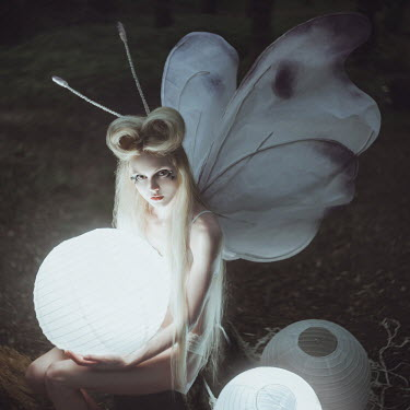 Anya Anti Young woman in moth costume holding lantern
