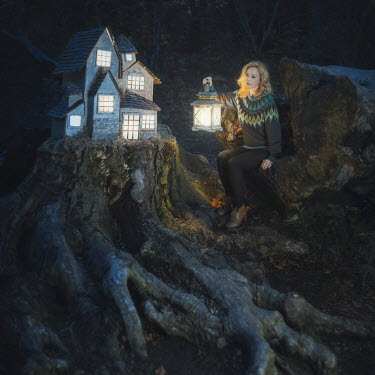 Anya Anti Young woman with lantern and house on tree stump
