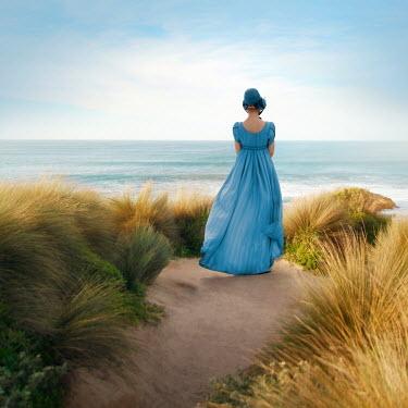 ILINA SIMEONOVA WOMAN IN BONNET STANDING BY IN DUNES BY SEA Women