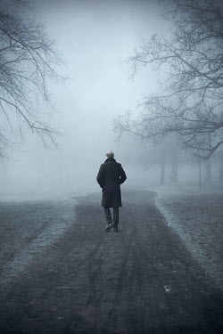 Miguel Sobreira Man in Black Coat Walking on Foggy Park Path