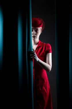 Magdalena Russocka retro woman in red behind blue curtains