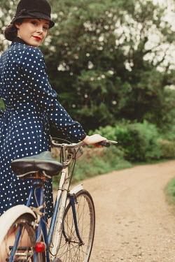 Shelley Richmond BRUNETTE WOMAN IN SPOTTY DRESS WITH BICYCLE Women