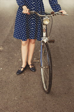 Shelley Richmond WOMAN IN SPOTTY DRESS WITH BICYCLE ON ROAD Women