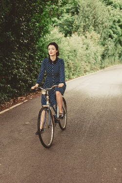 Shelley Richmond WOMAN IN SPOTTY DRESS RIDING BICYCLE IN COUNTRYSIDE Women
