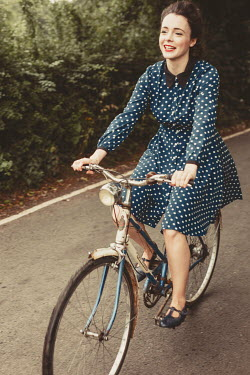 Shelley Richmond HAPPY WOMAN IN SPOTTY DRESS RIDING BICYCLE Women