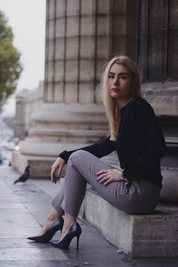 Anna Rakhvalova BLONDE WOMAN SITTING BY PILLAR OF CITY BUILDING Women