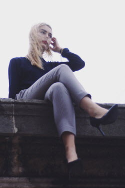 Anna Rakhvalova BLONDE WOMAN IN STILETTOS SITTING ON WALL Women