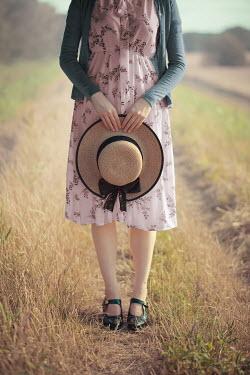 Ildiko Neer Vintage woman holding hat countryside