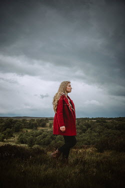 Shelley Richmond BLONDE WOMAN WITH RED COAT IN COUNTRYSIDE Women