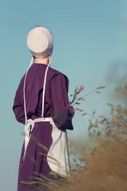 Magdalena Russocka historical woman wearing white bonnet in fields