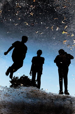 Ute Klaphake THREE SILHOUETTED TEENAGERS REFLECTED IN PUDDLE Groups/Crowds