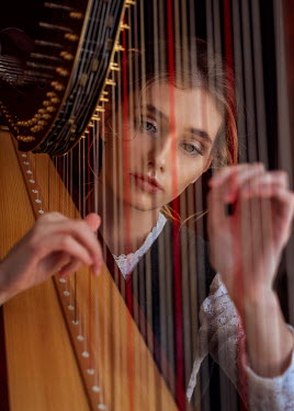 Anna Volynskaia SERIOUS WOMAN IN WHITE LACE PLAYING HARP Women