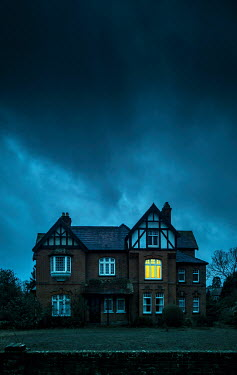Kyle Stubbs LIGHT IN WINDOW OF HOUSE WITH STORMY SKY Houses