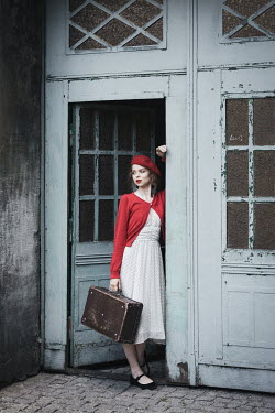 Dorota Gorecka Young woman with red beret and suitcase standing in doorway