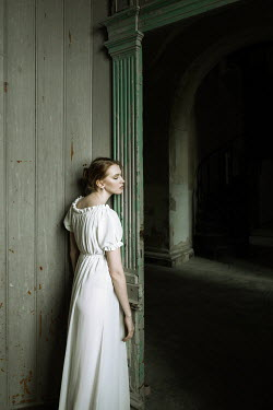 Dorota Gorecka Young woman in white dress standing in doorway of abandoned house