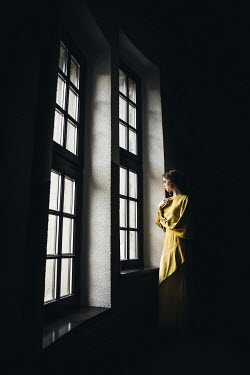 Dorota Gorecka Young woman in yellow dress by window