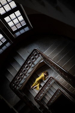 Dorota Gorecka Young woman in yellow dress lying on staircase from above